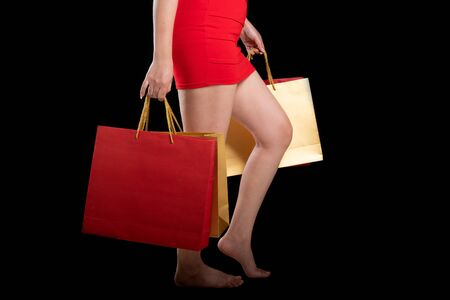 Portrait of a beautiful woman wearing a red dress holding shopping bags a black background, sale concept Stock Photo