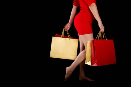 Portrait of a beautiful woman wearing a red dress holding shopping bags a black background, sale concept, copy space