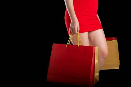 Portrait of a beautiful woman wearing a red dress holding shopping bags a black background, sale concept, copy space, side view
