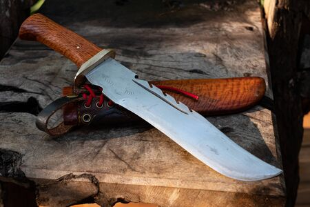 Large knife in leather and natural wood grain casing on table background handmade fo Thailand