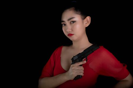Portrait beautiful Asia woman wearing a rad dress one hand holding pistol gun 11mm. at the black background, Young sexy girl long hair with a handgun look at the camera, Pretty women stand with a guns 스톡 콘텐츠