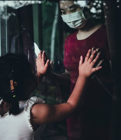 Mother wear face mask meeting daughter and touching hand through the window because of the quarantine Corona Virus Covid-19, social distancing Standard-Bild