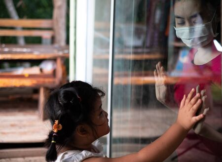 Mother wear face mask meeting daughter and touching hand through the window because of the quarantine Corona Virus Covid-19, social distancing