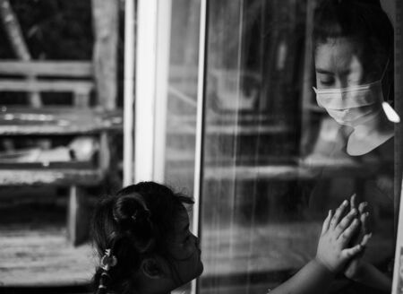 Mother wear face mask meeting daughter and touching hand through the window because of the quarantine Corona Virus Covid-19, social distancing, Black and white picture