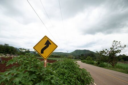 Yellow traffic signs warning against winding road ahead at green grass in the background