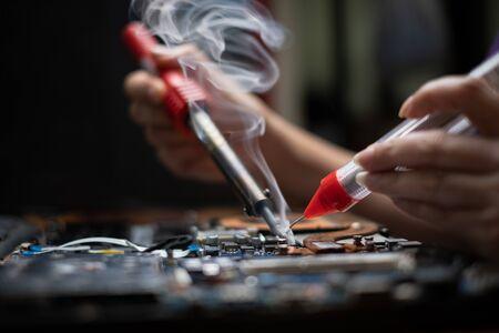 Close-up hand technician repairing broken laptop notebook computer with electric soldering Iron Banco de Imagens - 149191894