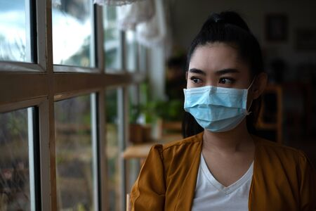 Young Asia woman sitting and putting on a medical mask to protect from virus infection airborne respiratory diseases at the cafe