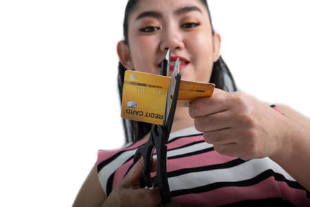 Portrait of young Asian woman cutting up a credit card with scissors to stop spending on shopping at the white background Stockfoto