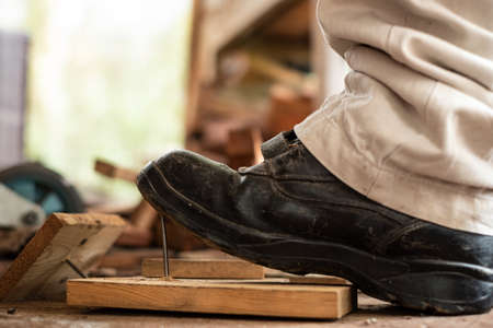 Worker in safety shoes stepping on nails on board wood In the construction area