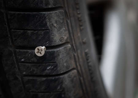 Close up button head needle metal screw nail stuck to puncture into wheel tire 写真素材