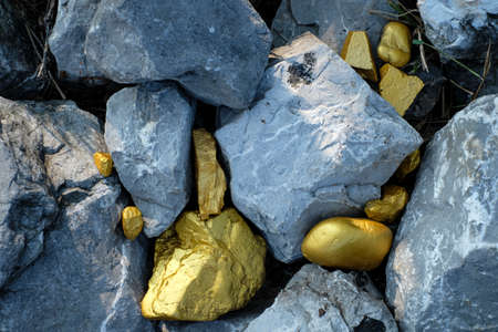 Gold nugget and grey granite stone background Banco de Imagens