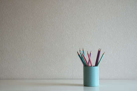 A book and pastel pencils in the blue glass on the desk at gray wall background
