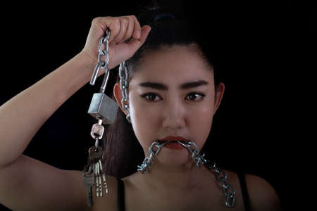 Portrait young Asia woman covered mouth by a steel chain and unlock to forbidden him the free speeching at the black background, Shut up or stop talking concept, Front view women