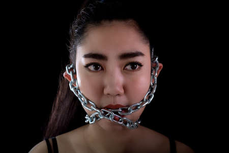 Portrait young Asia woman covered mouth by a steel chain and lock to forbidden him the free speeching at the black background, Shut up or stop talking concept, Front view women