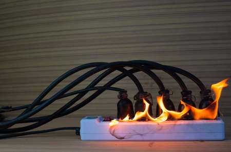 On fire multi socket with the connected power strip with a bunch of plugs on wood background