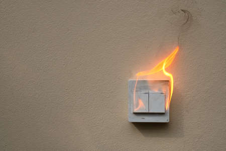 On fire switch electric shock on concrete wall Stock Photo