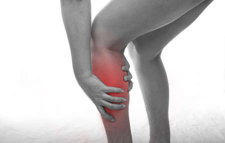 Woman with calf feeling pain on white background Imagens