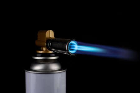 Flamethrower burner gas blow torch Ignition with blue fire flame at black background