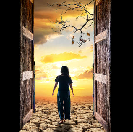 Woman walking into cracked soil in arid areas of the landscape through the open big door