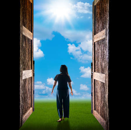 Woman walking into the light has cloud and sun through the open big door