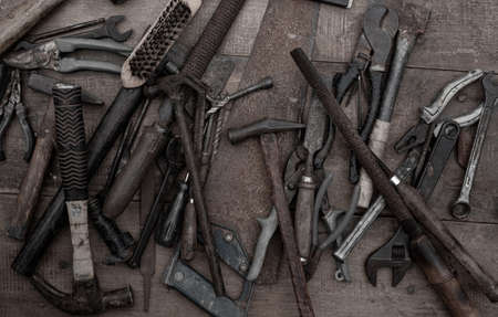 Collection of old woodworking handtools on a rough workbench wooden