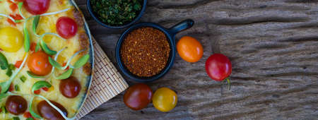 Close up homemade vegetable pizza with cherry tomatoes and other ingredients on a wooden background