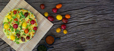 Homemade veggie pizza with cherry tomatoes and other ingredients on a wooden