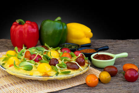 Homemade vegetable pizza with bell pepper cherry tomatoes and other ingredients on a wooden background Stockfoto