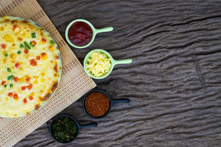 Homemade vegetable pizza with cherry tomatoes and other ingredients on a wooden