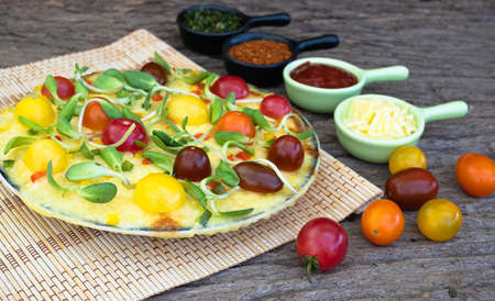 Homemade veggie pizza with cherry tomatoes and other ingredients on a wooden background Stockfoto