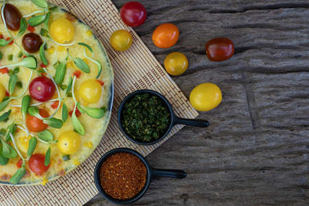 Homemade vegetable pizza with cherry tomatoes and other ingredients on a wooden background Stockfoto