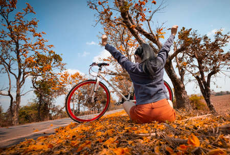 The back woman arms raised and sitting next to her bike outdoors at palash tree with full of beautiful orange flower background, Butea Monosperma or Butea frondosa of southeast asia from nature Stockfoto