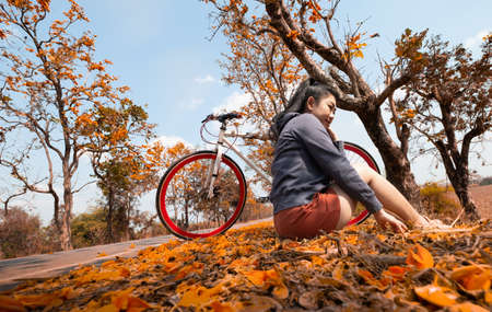Beautiful young asia woman sitting next to her bike outdoors at palash tree with full of beautiful orange flower background, Butea Monosperma or Butea frondosa of southeast asia from nature