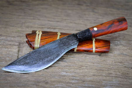 Damascus knife custom in the natural rosewood casing on old table background handmade of Thailand