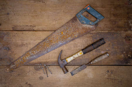Hammer saw and chisel Collection of woodworking old handtools on a rough workbench wooden Imagens