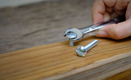 Close-up of a joiner hand with a wrench screwing nut a furniture screw into a wooden plank, The effort  wrong of tools as a fail concept Imagens