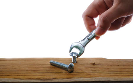 Close-up of a joiner hand with a wrench screwing a furniture screw into a wooden plank at white background, The effort  wrong of tools as a fail concept Imagens