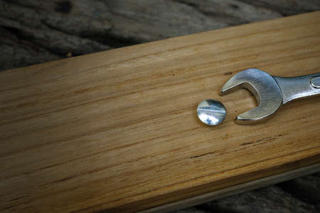 Close-up wrench screwing nut a furniture screw into a wooden plank, The effort  wrong of tools as a fail concept