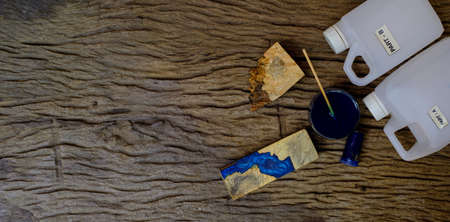 Mixing color blue epoxy resin in a glass cup for casting burl wood on old wooden table background