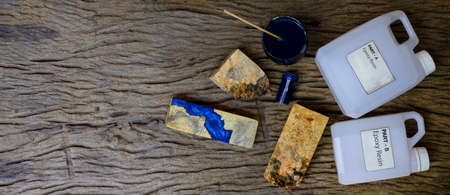 Mixing color blue epoxy resin in a glass cup for casting burl wood on old wooden background Imagens
