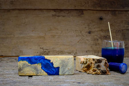Timber burl woodchips color bottle and resin epoxy for casting wood on old wooden table background Imagens