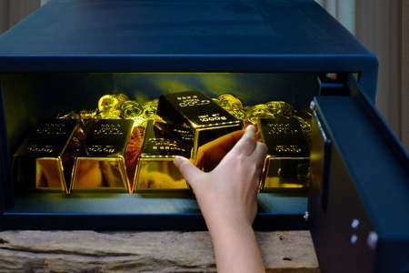 Hand open electronics steel safe box full of coins stack and gold bar