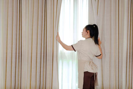 Young maid opening curtains in hotel room