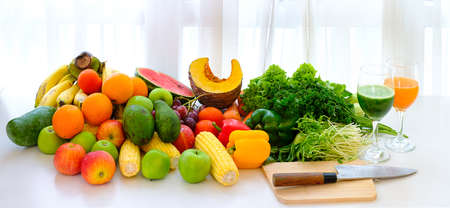 Assorted fresh ripe fruits and vegetables on the table at white curtain background, Food concept background