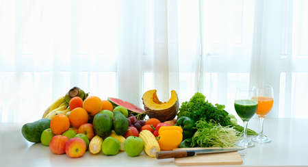 Assorted fresh ripe fruits and vegetables on the table at white curtain background, Imagens