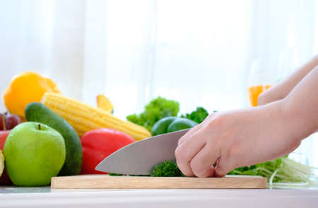 Hands using a knife chopping vegetable over wooden carving board on the table at white curtain background
