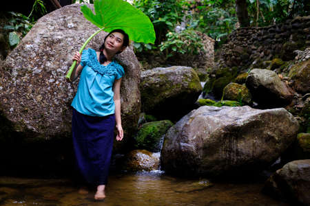 Portrait of young Asia woman standing with holding Bon leaves at the rock and waterfall background Imagens