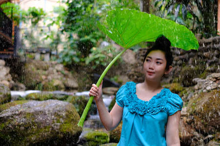 Portrait of a young Asia woman with black hair holding bon leaves in the raining at the rock and waterfall background Imagens
