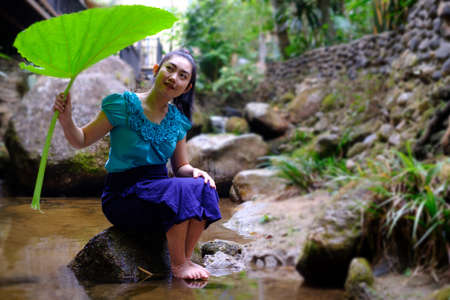 Portrait of young Asia woman sitting on a stone with holding Bon leaves at the rock and waterfall background Imagens