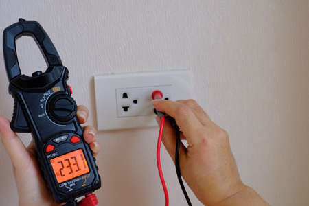 An electrician is a hand holding on the digital multimeter into a hole of an electric socket to  measure ac voltage